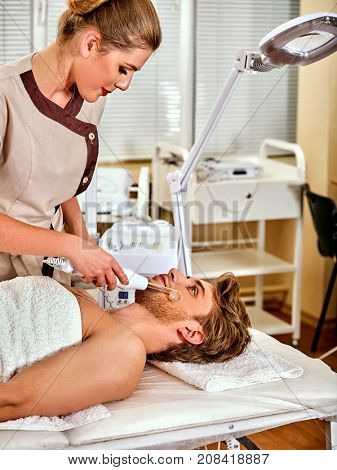 High frequency machine in spa salon. Man receiving electric darsonval facial massage after procedure at beauty room. Modern technologies and methods of rejuvenation. The best spa salon.