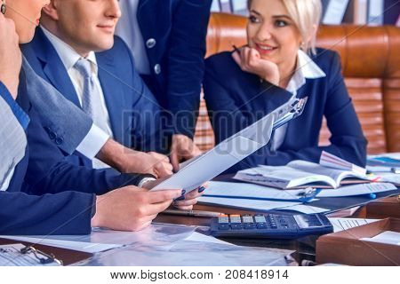 Business people office life of team people working with papers sitting table. Cabinets with folders background. Successful transaction lifted the mood of the employees.