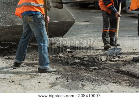 Workers cleaned the old asphalt with shovels and toss the asphalt into the tractor's scoop