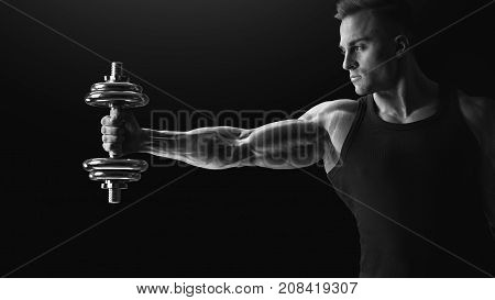 Black And White Photo Of Handsome Power Athletic Man In Training Pumping Up Muscles Holding Dumbbell