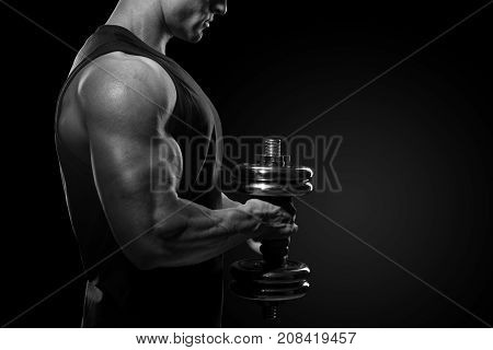 Close-up Of A Power Fitness Man Handsome Power Athletic Man In Training Pumping Up Muscles With Dumb