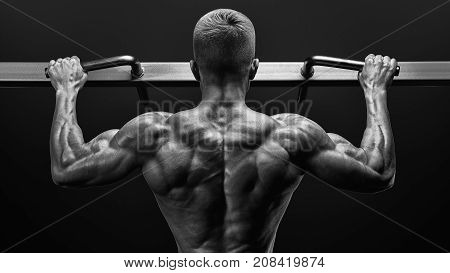 Power Muscular Bodybuilder Guy Doing Pullups In Gym. Fitness Man Pumping Up Lats Muscles. Fitness An