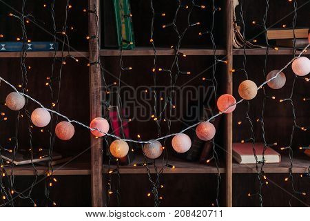 Christmas decor garland on wooden shelaves with books. New Year eve.