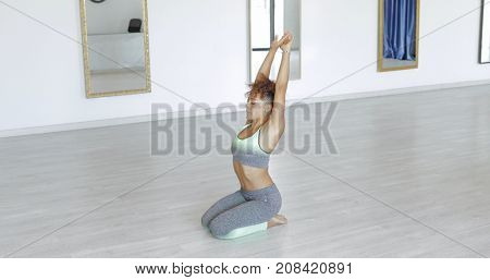 Concentrated young woman sitting on floor of studio meditating with hands up in harmony with eyes closed.