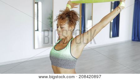 Young sportswoman training hands with help of elastic band while working out in modern studio and breathing with eyes closed.