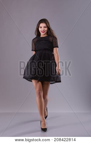 forward view of walking brunette woman in black dress. beautiful smiling girl in motion. frontview of person. over gray background. view people collection. Red lips and long legs