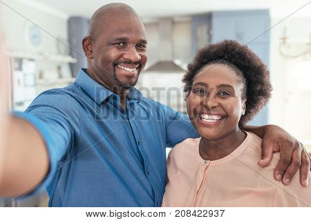 Portrait of a smiling African couple taking a selfie together while standing arm in arm together in their living room at home