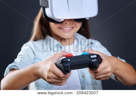 Virtual games. Modern game console being in use by a delighted sweet positive girl while playing virtual games