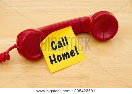Remember to call home Retro red phone handset with a yellow sticky note and text Call Home