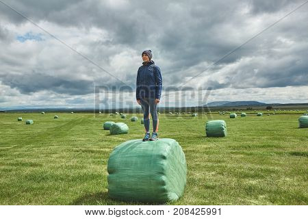 smiling woman traveler, wearing in outdoor clothing, stands on a hay bales in a field. Travel to Iceland. Hay bales in green plastic film stacked on a huge field.