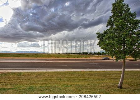 Approaching thunderstorm viewed from across a road and agricultural field near Chandler Arizona