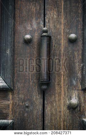 iron door hinge on old brown wooden doors close up