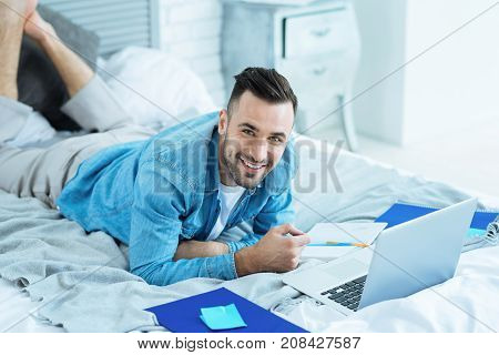What a wonderful day. Handsome young man looking into the camera with a cheerful smile on his face while lying in bed and preparing his home assignment at a laptop.