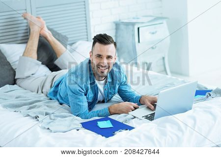 Comfortable workspace. Full of energy millennial guy grinning broadly while lying in bed and looking into the camera during a work session at home.