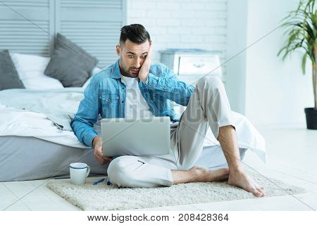 What is that. Horrified millennial guy holding his hand on his face and keeping his eyes wide opened while sitting on the floor and focusing his attention on a screen of a laptop.