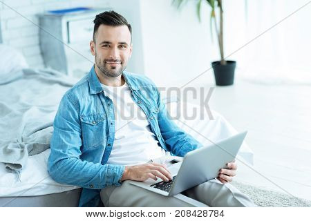 Comfortable workspace. Relaxed young man sitting on the floor with a laptop on his legs and looking into the camera with a slight smile on his face while working.