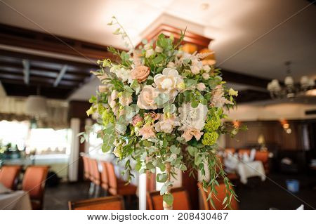 Beautiful and stylish bouquet of flowers as an indoor decoration in the bright restaurant hall