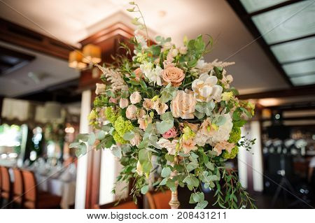 Beautiful and elegant bouquet of flowers as an indoor decoration in the bright restaurant hall