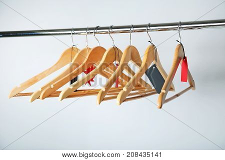 Sale tags on wooden hangers and grey background