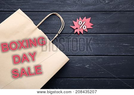 Red sale tag and shopping bag with inscription Boxing Day Sale on black wooden table