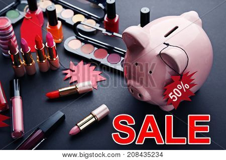 Red Sale Tags With Piggybank And Makeup Cosmetics On Black Background