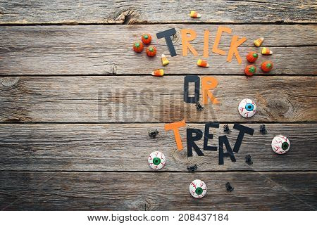 Halloween Candy Corns With Inscription Trick Or Treat On Wooden Table