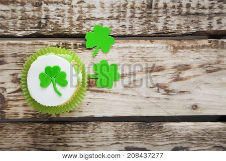 Green Paper Clover Leafs And Tasty Cupcake On A Grey Wooden Table