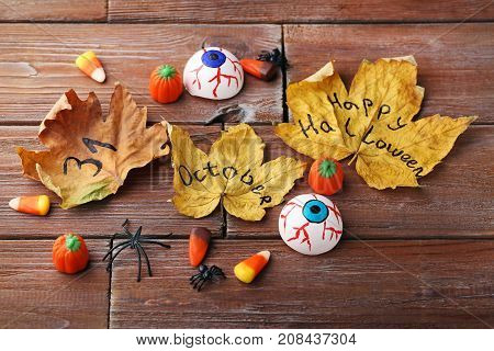 Halloween Candy Corns With Dry Leafs And Spiders On Wooden Table