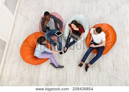 Group of young multiethnic friends using gadgets sitting indoors at university campus and working together on creative task, top view with copy space