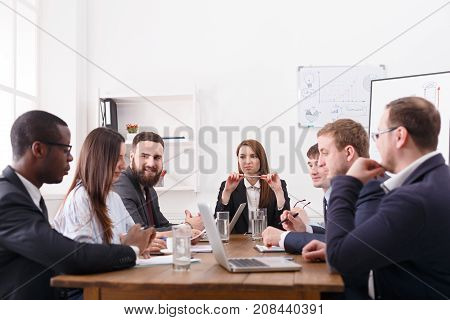 Official meeting, multiethnic friendly atmosphere, team with female boss. Discussion, communication with partners at the desk