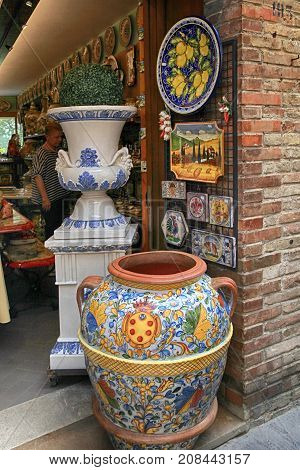 SAN GIMIGNANO, ITALY - JULY 22, 2017 : Shop with majolica ceramics at the medieval town of San Gimignano, Siena, Tuscany, Italy. Colourful pottery is a popular souvenir for tourists and is sold throughout the town of San Gimignano.
