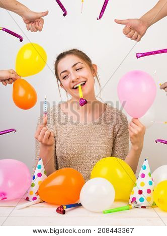 holidays, weekends, beauty concept. wonderful girl with charming smile with birthday whistle in her teeth, she is holding small pinl balloon and blue candle for cake