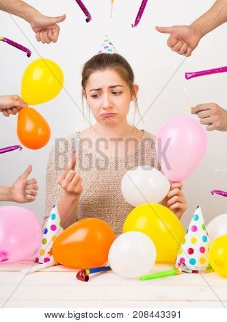 party, amusement, presents concept. disappointed and sad girl with curved lips, she is wearing knitted sweatshirt of beige colour and surrounded by attributes of celebration of birthday