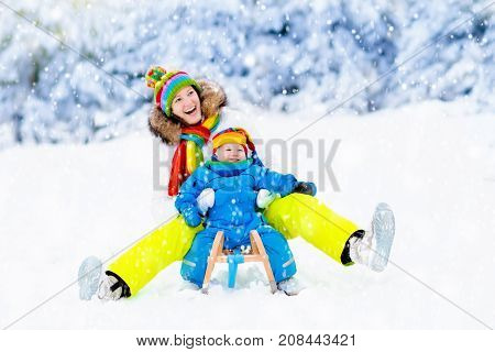 Mother and baby on sleigh ride. Child and mom sledding. Toddler kid riding sledge. Children play outdoors in snow. Kids sled in snowy park. Outdoor winter fun for family Christmas vacation.