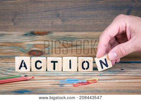 Action. Wooden letters on the office desk. Business and communication background.