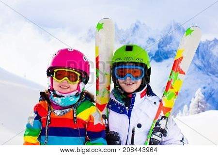 Kids skiing in mountains. Active children with safety helmet goggles and poles. Ski race for young kids. Winter sport for family. Child ski lesson in alpine school. Little skier racing in snow