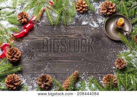 Christmas fir trees in snow with cones red ribbon and candle in candlestick on a dark wooden board. Copy space for your text
