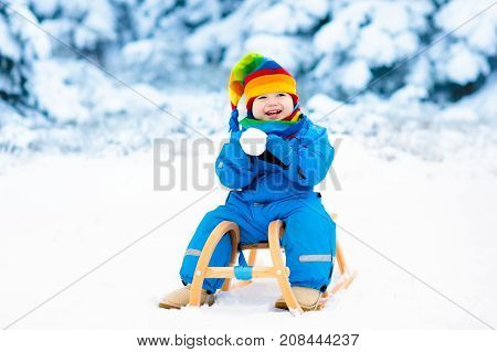 toddler kid riding a sledge children play outdoors in snow kids sled in the alps mountains in winter outdoor fun for family christmas vacation - Christmas Vacation Sled