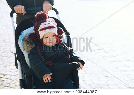 Cute smiling child boy in a funny hat in stroller spending winter holidays with family at the Christmas market in Cesky Krumlov Czech Republic Europe. poster