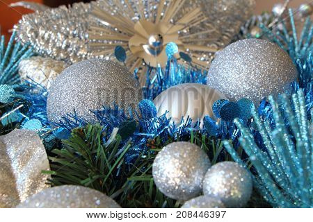 Silvery Christmas balls and blue tinsel on an artificial Christmas wreath