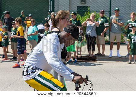 Green Bay WI - August 1 2017: Green Bay Packer Damarious Randall rides a young fans bike after football practice. The community owned team has a long tradition of player involvement with fans.