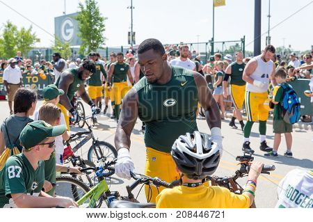 Green Bay WI - August 1 2017: Green Bay Packer Kenny Clark rides a young fans bike after football practice. The community owned team has a long tradition of player involvement with fans.