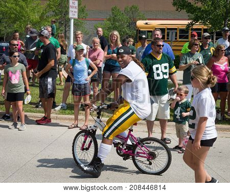 Green Bay WI - August 1 2017: Green Bay Packer Kalif Phillips rides a young fans bike after football practice. The community owned team has a long tradition of player involvement with fans.