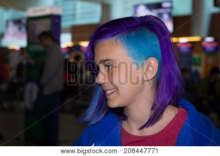Smiling girl in the interior of the airport in extreme hair color