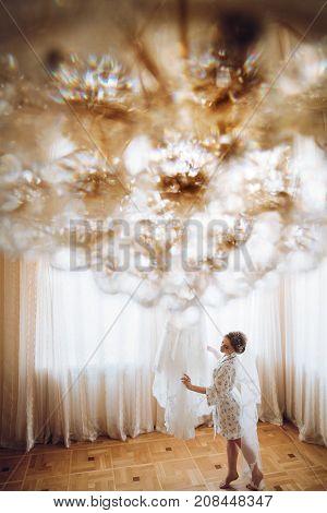 Beautiful Happy Bride Walking To Her Luxury Wedding Dress By The Window, Standing In Silk Robe. Happ