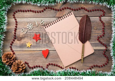 Christmas or new year frame for your project with copy space on blank notebook. Christmas green spangle with cones 2017 fugures stars and snowflake. Blank notebook with qull feather pen for your text.