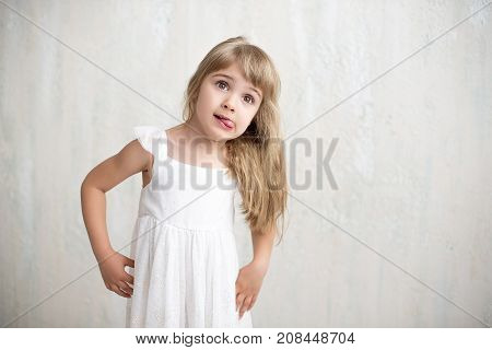Portrait Of Pretty Little Girl In White Dress , She Is Smiling And Showing Tongue. She Is Happy And
