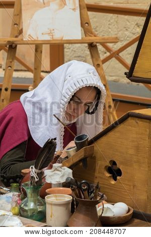 Medieval reenactor in scribe costume practicing traditional illumination writing calligraphy with feather quill and ink, Mdina, Malta, April 2017