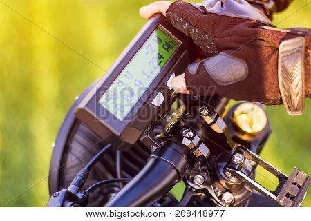 Close up of man hand clicking on mode button on monitor electric bike. Ebike bicycle environmentally friendly eco e-mountainbike transport. Healthy lifestyle