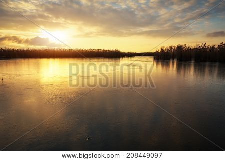 Winter landscape with frozen river and sunset sky. Composition of nature.